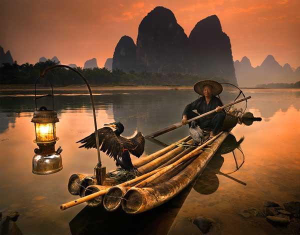 Рыбак со своим бакланом готов отправиться за рыбой. Фото Brendan Haywood
